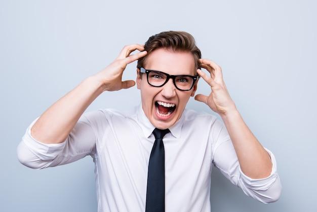 Gek en gek worden. close-up portret van geschreeuw beklemtoonde jonge ondernemer in formele slijtage en glazen, staande op pure lichte ruimte