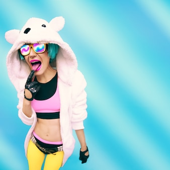 Gek feestmeisje in hoodie beer op een blauwe achtergrond. positieve emoties