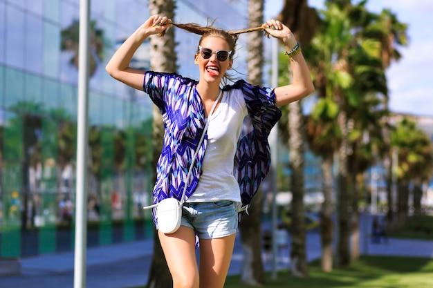 Gek gelukkig portret van vrouw die grappige gezichten maakt, geniet van haar hete zomerdagen in het weekend, heldere hipster trendy kleding, leg haar handen in de lucht en ontspan, exotisch land.