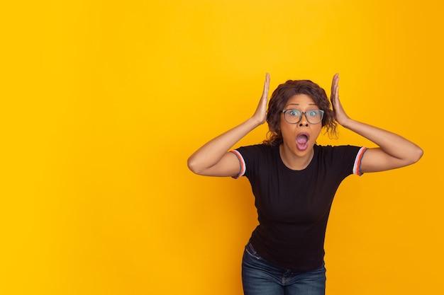 Gek geschokt met hoofd in handen. afro-amerikaanse jonge vrouw portret geïsoleerd op gele studio achtergrond. mooi krullend model. concept van menselijke emoties, gezichtsuitdrukking, verkoop, advertentie, jeugd.
