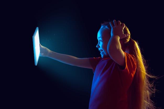 Gek gewonnen. kaukasisch meisje portret op donkere muur in neonlicht. mooi vrouwelijk model dat tablet gebruikt. concept van menselijke emoties, gezichtsuitdrukking, verkoop, advertentie, moderne technologie, gadgets.