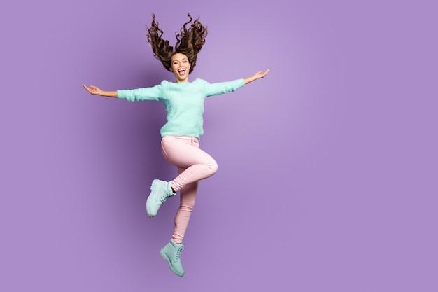 Gek grappig schattig meisje sprong handen vasthouden geniet van de overwinning waait in haar kapsel draag roze broek zachte pastelkleurige pullover schoeisel.