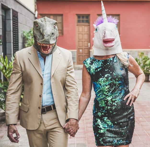 Gek hoger paar dat rond stadsstraat loopt die t -t-rex en kippenmasker draagt