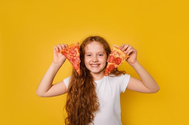Gek krullend meisje houdt twee plakjes pizza bij haar ogen en steekt haar tong uit.