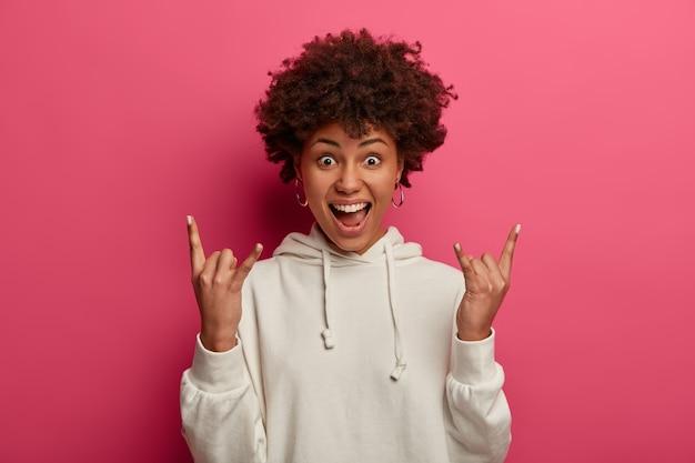 Gek meisje met donkere huid wordt wild, woont rockconcert bij, maakt heavy metal-bord, roept luid uit, draagt sweatshirt, voelt zich enthousiast en opgewonden, draagt witte hoodie, geïsoleerd op roze muur