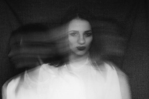 Gek portret van meisje met psychische stoornissen en gespleten persoonlijkheid, zwart en wit met extra korrel en bewegingsonscherpte