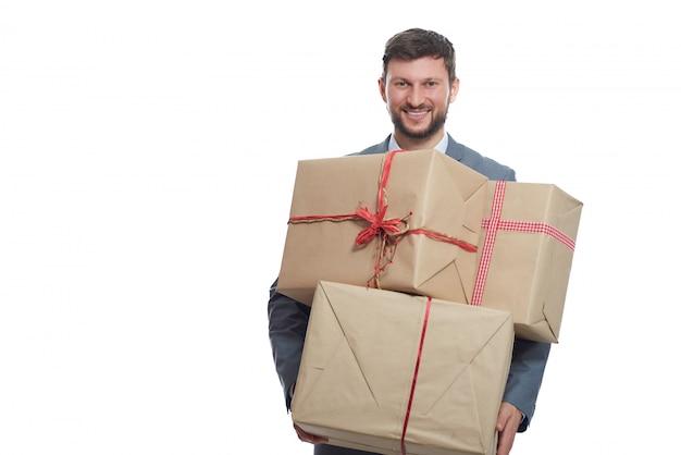 Gek shoppen op valentijnsdag. knappe gebaarde jonge mens die warm aan camera het stellen met giften glimlacht.