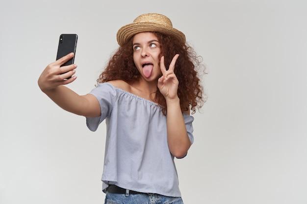 Gek uitziende vrouw, meisje met rood krullend haar. gestreepte blouse en hoed met blote schouders. maak een selfie op een smartphone, toon vredesteken en tong. tribune geïsoleerd over witte muur