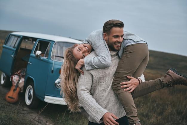 Gek worden. knappe jonge man die zijn aantrekkelijke vriendin op de schouders draagt en glimlacht terwijl hij in de buurt van de blauwe minibus in retrostijl staat