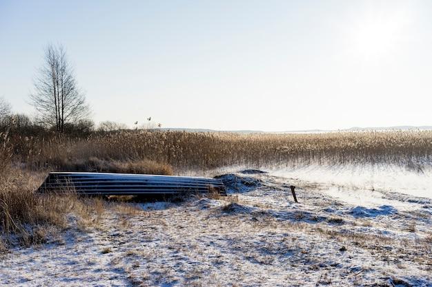 Gekantelde boot in de buurt van het bevroren meer in de winter tegen de zon