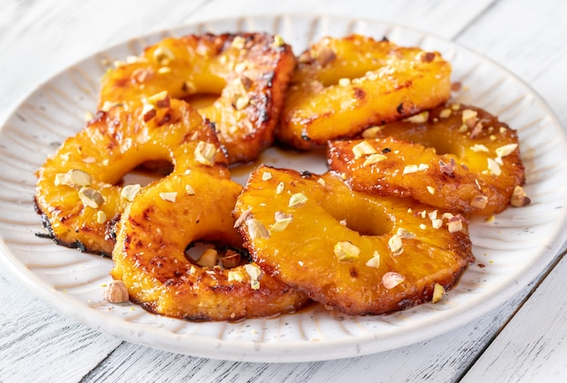 Gekarameliseerde ananas met slagroom en pistachenoten op de serveerschaal