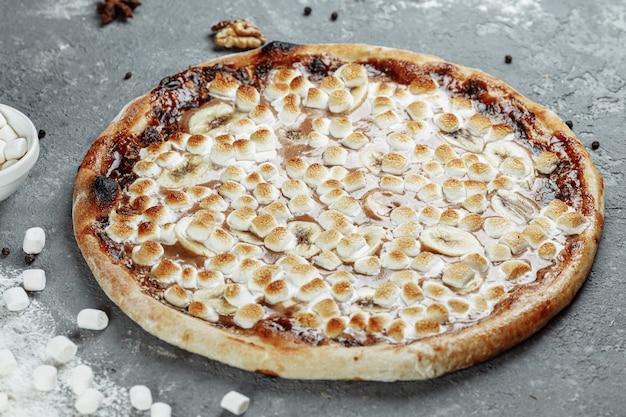 Gekarameliseerde banaan met hazelnootpasta pizza. ingrediënten zijn pizzadeeg, gesneden banaan en hazelnootpasta. zoet en krokant.