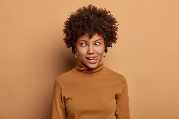 Gekke afro-amerikaanse vrouw maakt grappig gezicht, steekt tong uit en kruist ogen, dwazen rond, draagt casual bruine coltrui