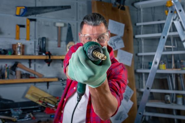Gekke agressieve gekke gekke jongeman in geruit hemd, veiligheidsbril op voor bescherming, handschoenen boren met boormachine, werken in timmerwerkplaats