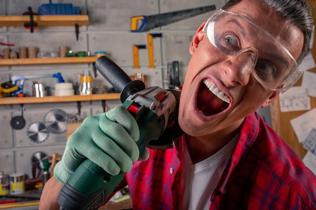 Gekke agressieve gekke gekke jongeman in geruit hemd, veiligheidsbril op voor bescherming, handschoenen met cirkelzaag in de timmerwerkplaats