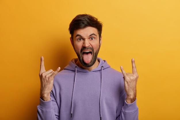 Gekke bebaarde hipster geniet van rockfeest, maakt heavy metal-bord, geniet van coole muziek, roept uit, brengt positieve vibes, gekleed in paars sweatshirt, geïsoleerd op gele muur, steekt tong uit