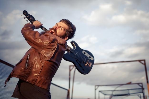 Gekke bebaarde man met grijs haar in een bruinleren jas zwaait met een zwarte elektrische gitaar tegen de lucht