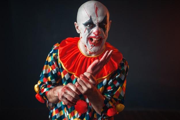 Gekke bloedige clown houdt menselijke hand, vinger in zijn tanden. man met make-up in halloween-kostuum, gekke maniak