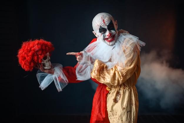 Gekke bloedige clown houdt menselijke schedel in rode pruik, horror. man met make-up in carnavalskostuum, gekke maniak