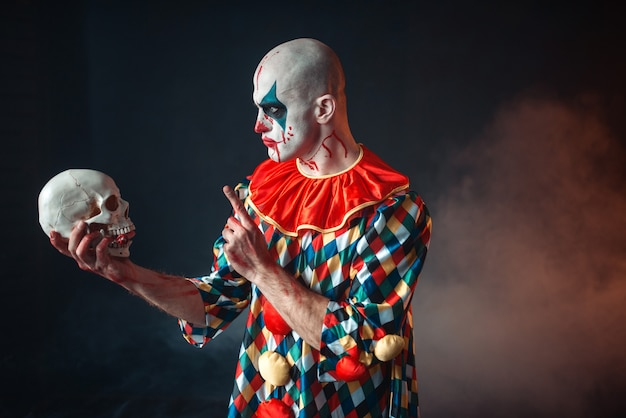 Gekke bloedige clown houdt menselijke schedel in rode pruik