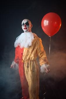 Gekke bloedige clown met make-up in carnaval kostuum houdt luchtballon, gekke maniak, eng monster