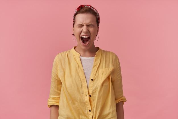 Gekke boze jonge vrouw in geel overhemd met hoofdband op hoofd die zich met gesloten ogen bevindt en over roze muur schreeuwt