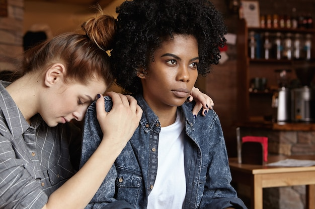 Gekke boze zwarte vrouw gekleed in een spijkerjasje pruilen, excuses negerend