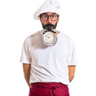 Gekke chef-kok die een klok over witte achtergrond houdt