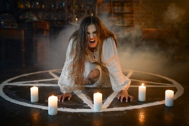 Gekke demonische vrouw zit in magische cirkel met kaarsen, demonen uitwerpen. exorcisme, mysterie, paranormaal ritueel, duistere religie, nachthorror, drankjes op de plank