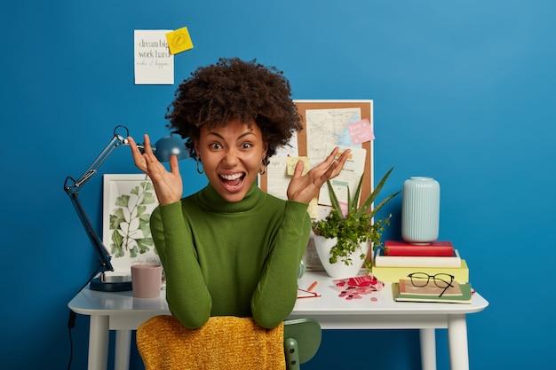 Gekke donkere jonge vrouw steekt zijn handen op van ergernis, draagt vrijetijdskleding, voelt zich moe, heeft een deadline, vormt op stoel in de buurt van witte tafel, geïsoleerd op blauwe achtergrond.