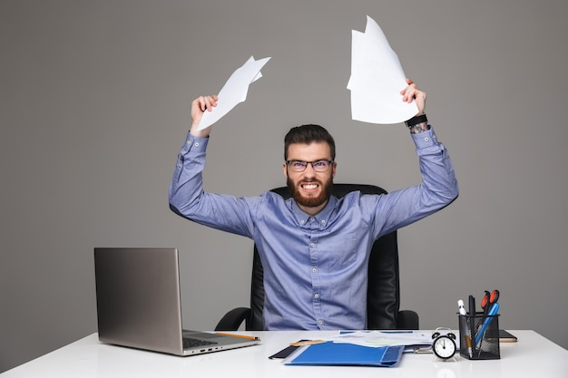 Gekke, elegante man met een baard in een bril die documenten vasthoudt en direct kijkt terwijl hij bij de tafel op kantoor zit