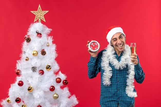 Gekke emotionele jonge kerel met kerstman hoed en met een glas wijn en klok staan