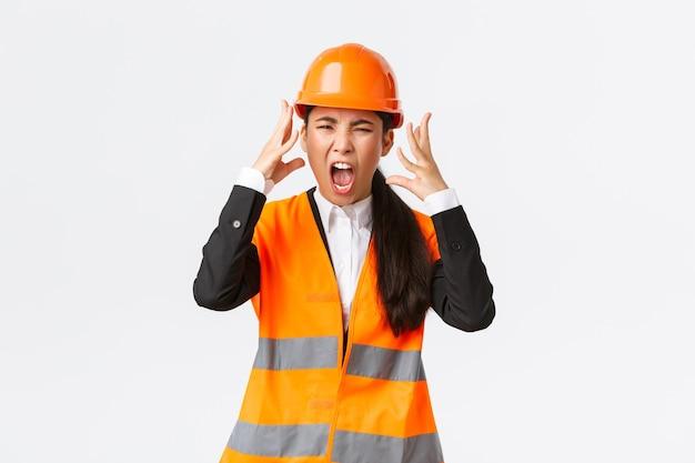 Gekke en verontwaardigde aziatische vrouwelijke hoofdingenieur, bouwmanager barstte in woede uit, verloor zijn geduld tegen werknemers, schreeuwde en schudde agressief de hand, schreeuw woedend als iemand uitschelden