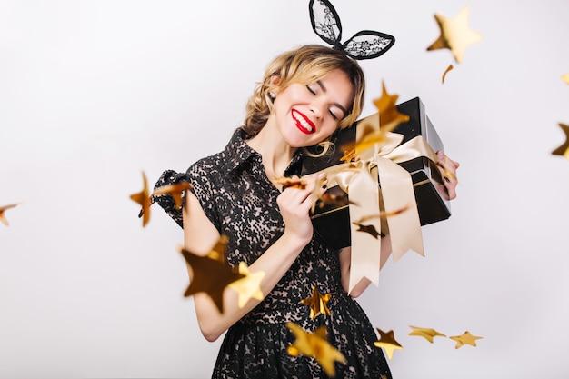 Gekke feesttijd van mooie vrouwen in elegante zwarte jurk met geschenkdoos, verjaardag, sprankelende gouden confetti, plezier, dansen. emotie gezicht, rode lippen, ogen dicht.