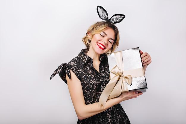 Gekke feesttijd van mooie vrouwen in elegante zwarte jurk met geschenkdoos verjaardag vieren, plezier maken, dansen. emotie gezicht, rode lippen, ogen dicht.