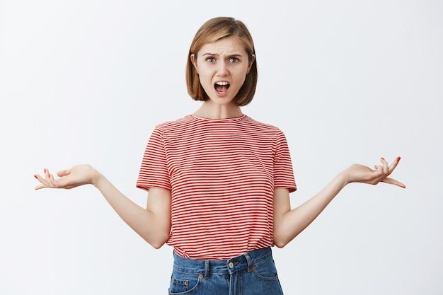 Gekke gecompliceerde jonge vrouw die er verward en gekweld uitzag en klaagde