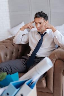 Gekke gedachten. emotioneel nerveus, uitgeputte man die in een fauteuil zit en gek wordt nadat hij de beste baan in zijn leven heeft verloren terwijl zijn vingers zijn voorhoofd raken