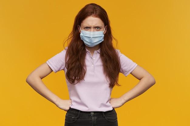 Gekke geïrriteerde jonge vrouw die een medisch beschermend masker draagt, houdt de handen op de taille over de gele muur