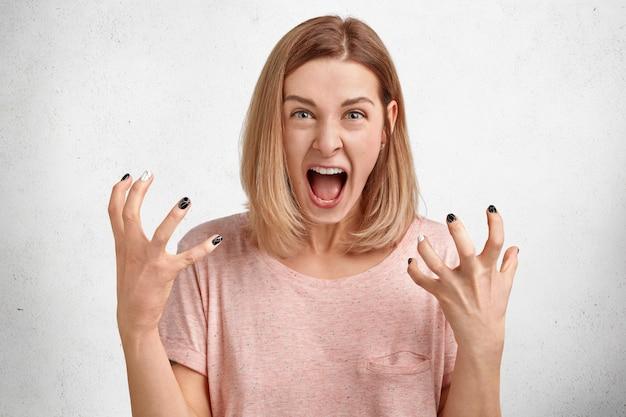 Gekke geïrriteerde jonge vrouw schreeuwt luid en gebaart actief, ontevreden en geïrriteerd door iets, drukt haar ongenoegen en ergernis uit
