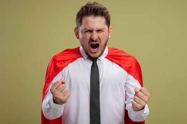 Gekke, gekke en boze superheld zakenman in rode cape balde vuisten met agressieve uitdrukking wild schreeuwen staande over groene muur