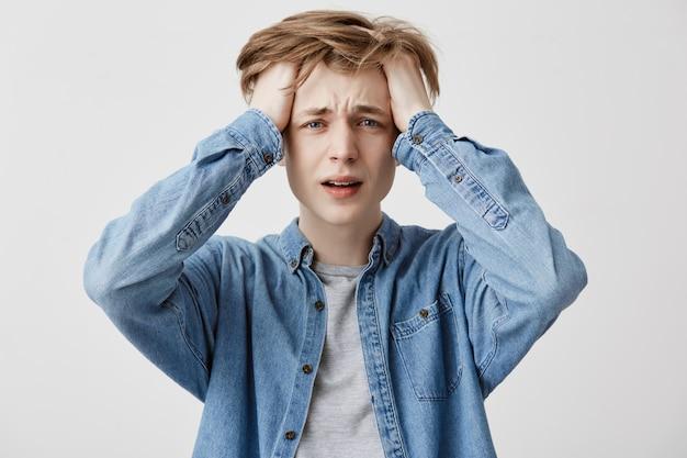 Gekke gekke, overstuur kerel heeft spijt van fouten, gekleed in een spijkerblouse, begrijpt dat hij niets kan veranderen of de tijd terug kan keren om de situatie te verbeteren, in paniek en stress. grote wanhoop
