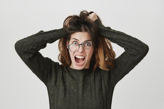 Gekke gekke vrouw warrig haar en schreeuwend van woede, draag een kromme bril