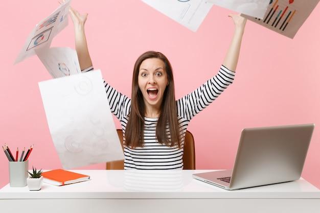 Gekke gelukkige vrouw die papieren documenten overgeeft terwijl ze aan een project werkt, op kantoor zit met laptop, op vakantie gaat geïsoleerd op roze achtergrond. prestatie zakelijke carrière concept. ruimte kopiëren.