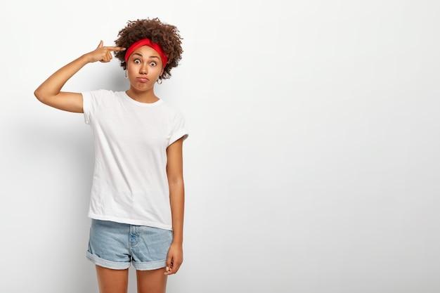 Gekke grappige afro-meisje schiet in tempel met vinger, gebaren binnen