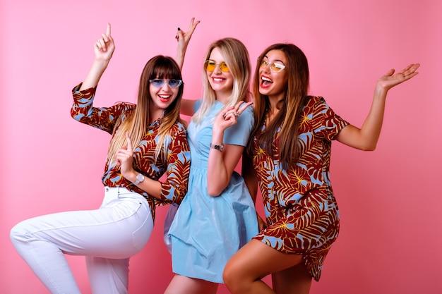Gekke grappige foto van drie gelukkige beste vriendenmeisjes die samen genieten van een feestje, dansen en lachen, kleuraanpassing trendy elegante outfits en glazen, positieve stemming, roze muur