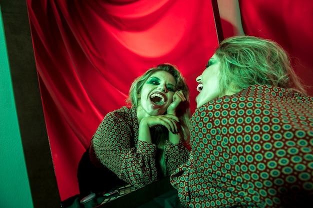 Gekke halloween-clownvrouw die bij de spiegel lachen