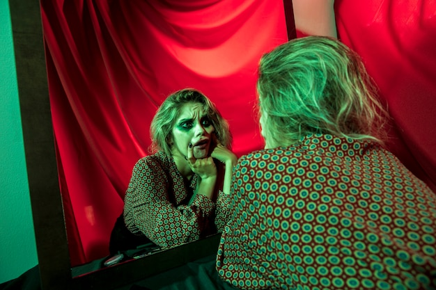 Gekke halloween-clownvrouw die zich bekijkt