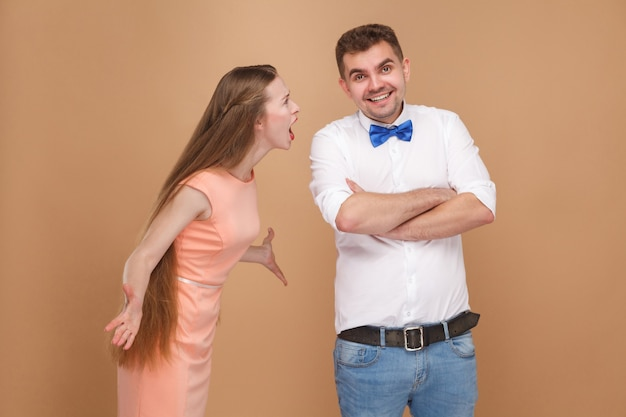 Gekke jonge blonde vrouw met lang haar in roze jurk die staat en tegen de man schreeuwt?