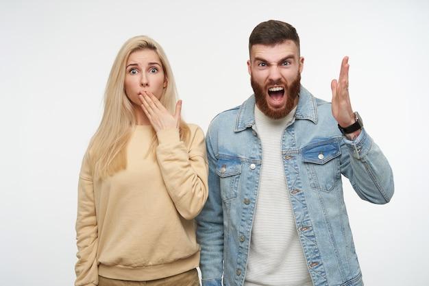 Gekke jonge mooie brunette man met baard emotioneel zijn hand opheffen terwijl boos schreeuwen, poseren op wit met verbijsterde blauwogige blonde dame kegelvormige haar mond