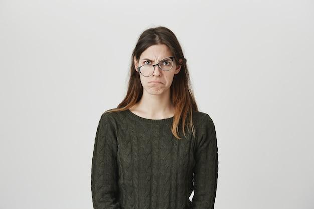 Gekke jonge vrouw die boos fronst en pruilt, draagt een kromme bril